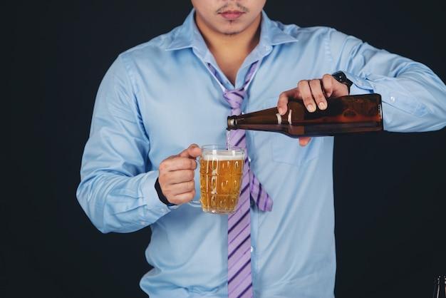Homme asiatique buvant une chope de bière