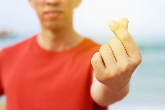 Homme asiatique en chemise orange montre signe de coeur coréen