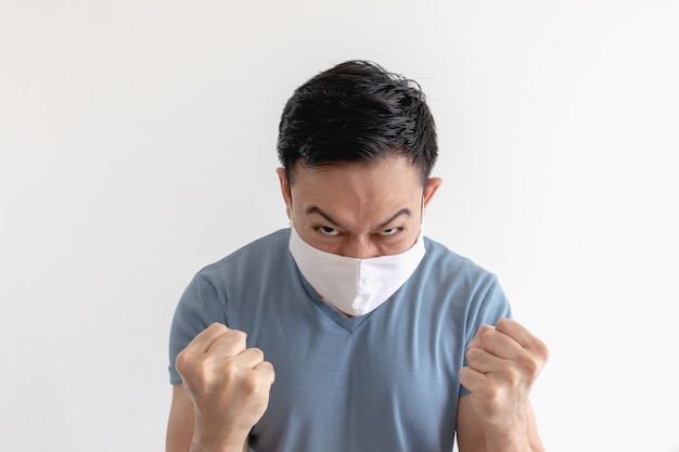 Homme asiatique en colère et fou dans un masque facial sur fond blanc isolé.