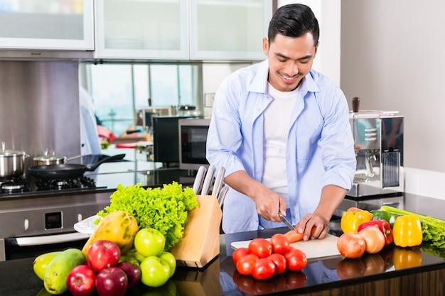 Homme asiatique, couper les légumes dans la cuisine domestique, préparer la salade