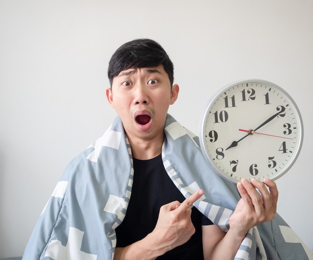 L'homme asiatique couvre le point de couverture à l'horloge dans sa main avec un visage choqué concept tardif fond blanc