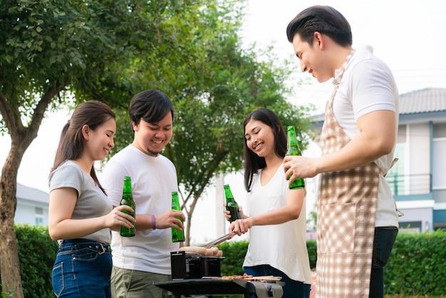 Homme asiatique cuisson barbecue grill et saucisse pour un groupe d'amis pour manger la fête dans le jardin à la maison.