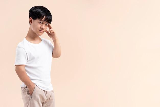 Homme asiatique dans une chemise blanche avec le nanisme posant