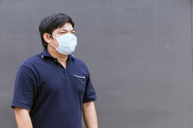 Homme asiatique dans la rue portant des masques de protection, homme malade avec masque de grippe.