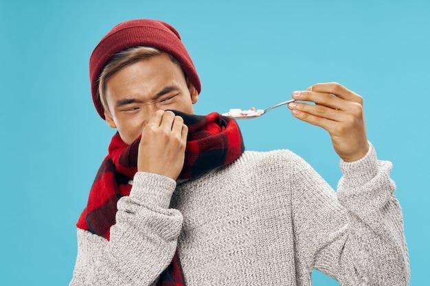 Homme asiatique dans des vêtements d'hiver chauds rejetant la nourriture