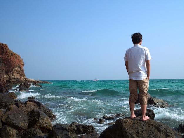 Homme asiatique debout sur la pierre de la côte de la mer