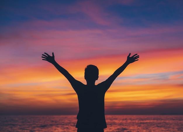 Homme asiatique debout sur la plage au bord de la mer au ciel du matin avec fond de lever de soleil.