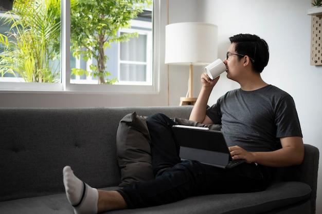Homme asiatique décontracté assis sur un canapé confortable à la maison et buvant du café le matin.