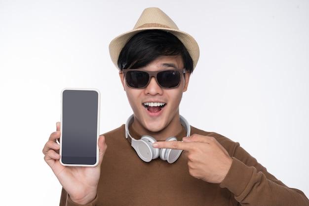 Homme asiatique décontracté intelligent assis sur une chaise, montrant l'écran du smartphone en arrière-plan studio