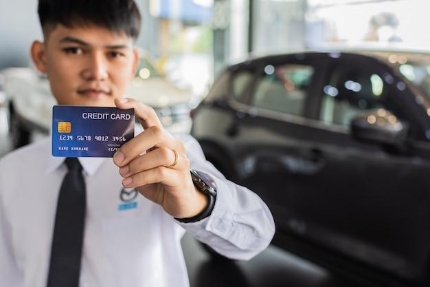 Homme asiatique détenant une carte de crédit pour voiture flou fond bokeh e-shopping marketing numérique