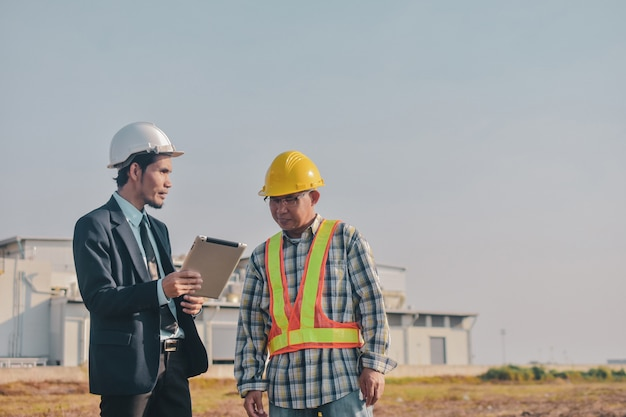 Homme asiatique, deux personnes, utilisation commerciale, contrôle de la tablette sur la construction du site