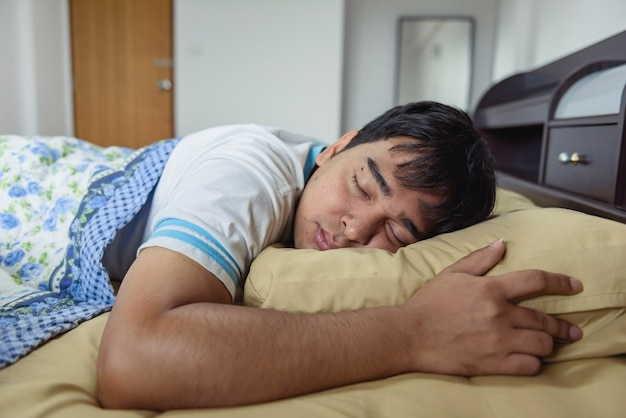 L'homme asiatique dort dans le lit.