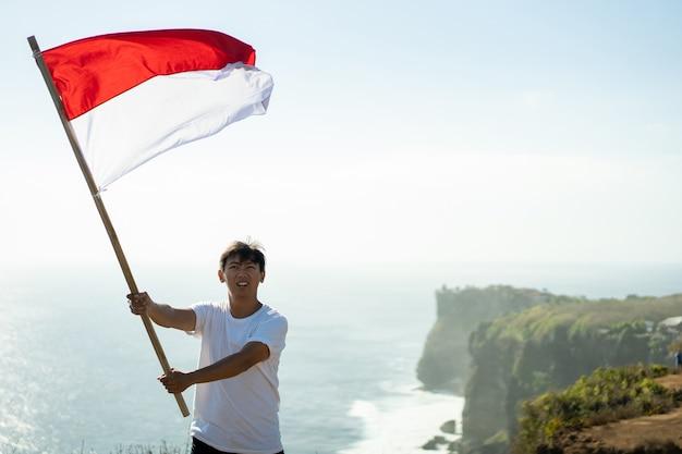 Homme asiatique avec drapeau indonésien de l'indonésie au sommet de la montagne