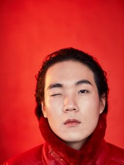 Homme asiatique drôle dans des vêtements rouges sur un espace rouge avec un œil fermé.