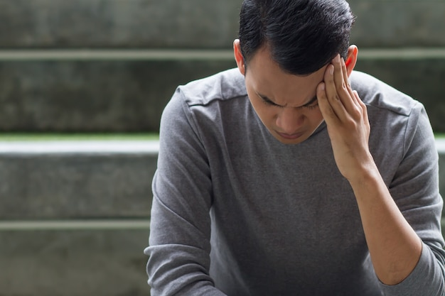 Homme asiatique du sud-est malade avec maux de tête, dépression, stress