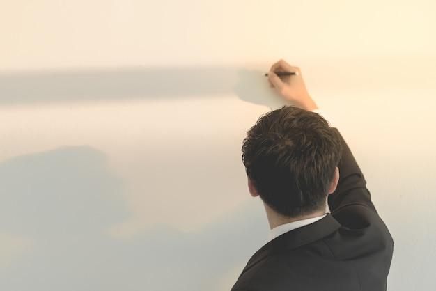 Homme asiatique écrire sur le tableau blanc