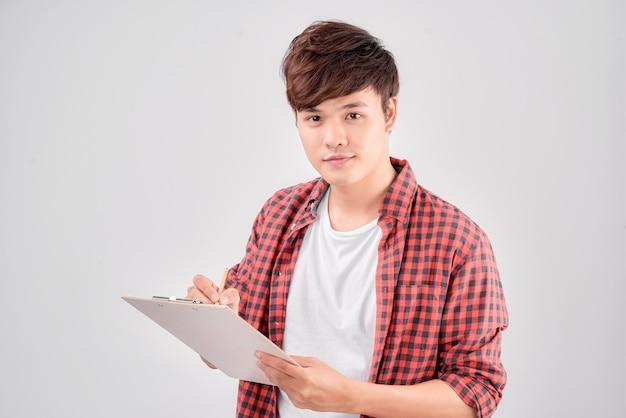 L'homme asiatique écrit sur le presse-papiers