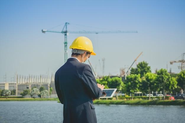 Homme asiatique ou enquête d'homme d'affaires sur la construction immobilière de site
