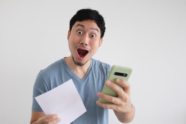L'homme asiatique est choqué par la facture et le smartphone sur un mur isolé.