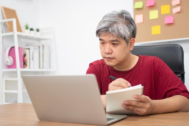 Homme asiatique étudie pour de nouvelles compétences à partir d'internet à la maison