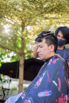 Homme asiatique faisant une coupe de cheveux pour rafraîchir son apparence à la maison. salon et salon de coiffure dans le jardin. nouveau mode de vie normal.
