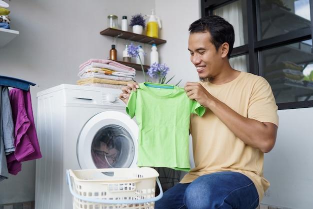 Homme asiatique faisant la lessive à la maison chargement des vêtements dans la machine à laver