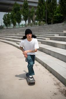 Homme asiatique faisant de la planche à roulettes dans la ville