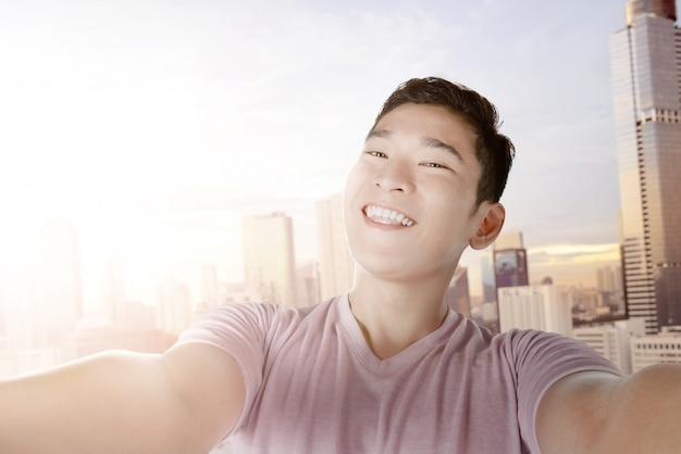 Homme asiatique faisant selfie avec son smartphone