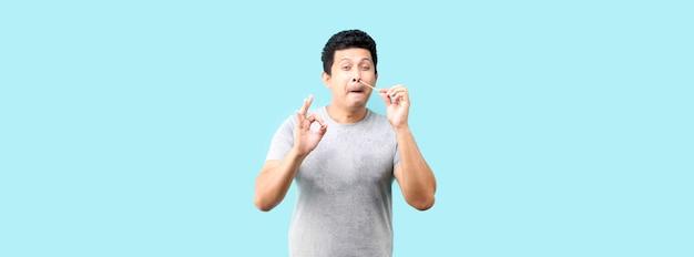 Un homme asiatique fait un autotest pour covid 19 sur fond bleu