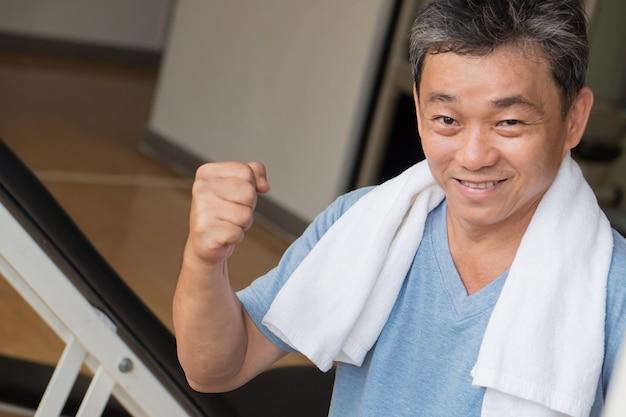 Homme asiatique fort, sain, heureux, souriant, positif, bien-être senior, travaillant dans une salle de sport
