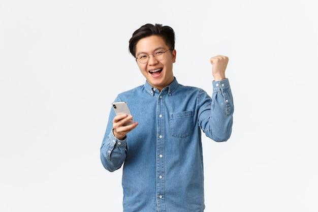Homme asiatique gagnant réussi dans des verres se réjouissant, pompe à poing satisfaite et souriante comme niveau de finition, jouant à un jeu mobile ou obtenu une date sur l'application de rencontres, triomphant ravi sur fond blanc