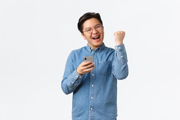 Un homme asiatique gagnant satisfait et réussi dans des lunettes et des bretelles se réjouissant, une pompe à poing ravie et souriante alors qu'elle réagit pour gagner dans un jeu mobile, reçoit des commentaires positifs sur l'application, fond blanc