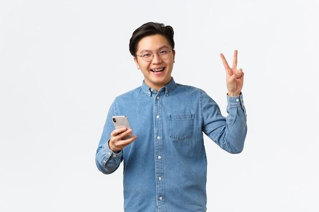 Un homme asiatique gai avec des bretelles, portant des lunettes et une chemise, utilisant un téléphone portable, une application pour smartphone, fait un geste kawaii de paix et souriant à la caméra, debout sur fond blanc