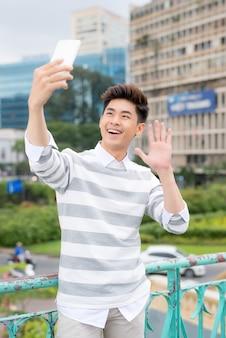 Un homme asiatique gai prenant un selfie sur un smartphone moderne tout en profitant d'une agréable promenade dans un parc public, portrait