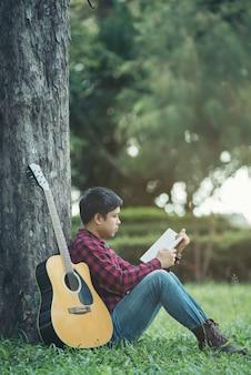 Homme asiatique avec une guitare acoustique dans un parc