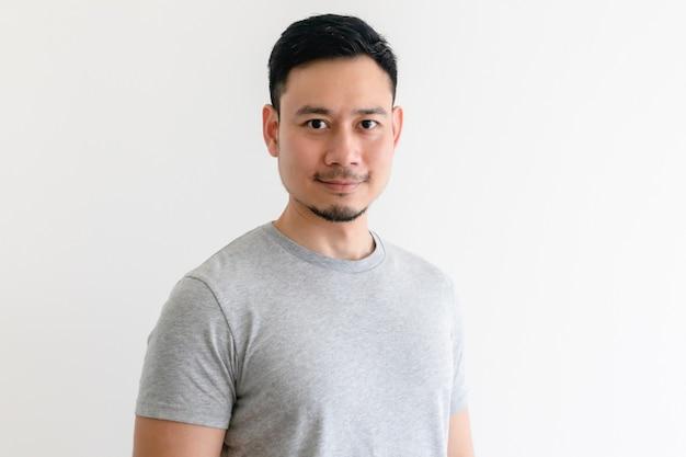 Homme asiatique heureux et confiant en t-shirt gris sur un espace blanc isolé.