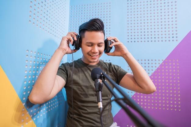 Un homme asiatique heureux enregistre un podcast dans son studio