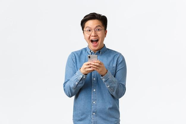 Un homme asiatique heureux et excité réagissant de bonne humeur aux nouvelles géniales lues en ligne, tenant un téléphone portable et semblant ravi de l'événement à venir. guy télécharger une nouvelle application ou un nouveau jeu cool, fond blanc.