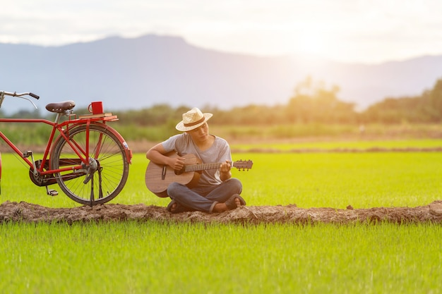 Homme asiatique, jouer de la guitare dans le champ de riz vert au coucher du soleil