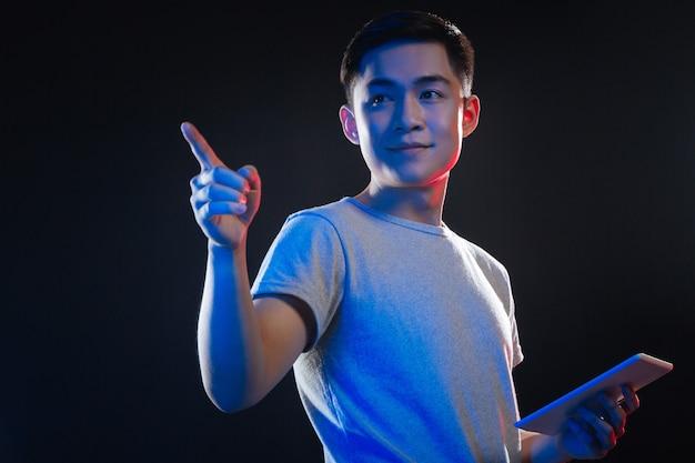 Homme asiatique joyeux à l'aide d'un appareil moderne tout en regardant le sensoriel