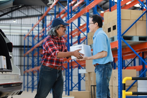 Homme asiatique livraison bonne boîte au client en usine et signature sur tablette sourire et bon service, concept de magasinage logistique en ligne