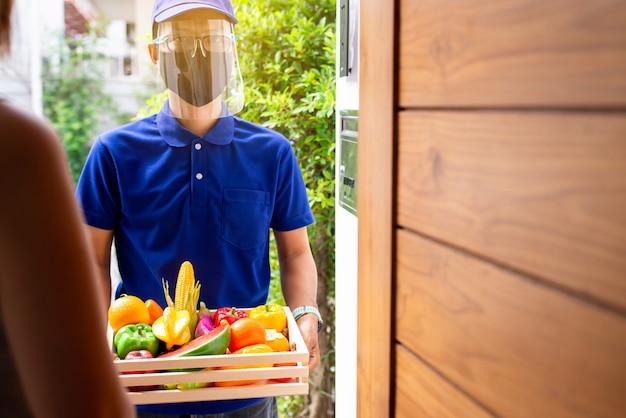Un homme asiatique de livraison tenant des légumes et des fruits frais dans une caisse prépare l'envoi au client à la maison