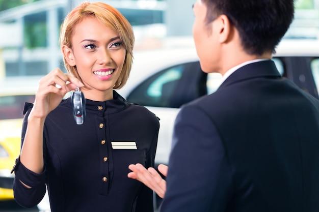Homme asiatique à la location de voiture clé de réception