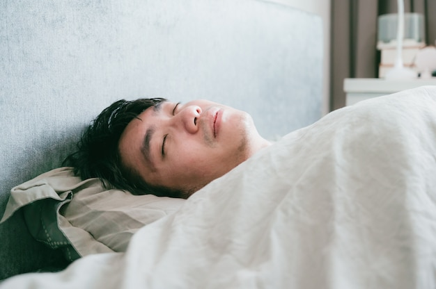Homme asiatique malade dort sur le lit. homme patient au repos de la maladie.