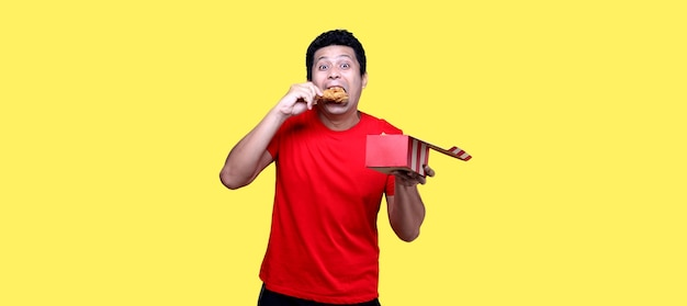 L'homme asiatique mange délicieusement du poulet frit sur fond jaune