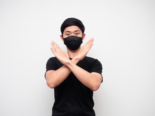 Homme asiatique avec masque bras croisés en désaccord dire non en regardant la caméra sur fond blanc isolat