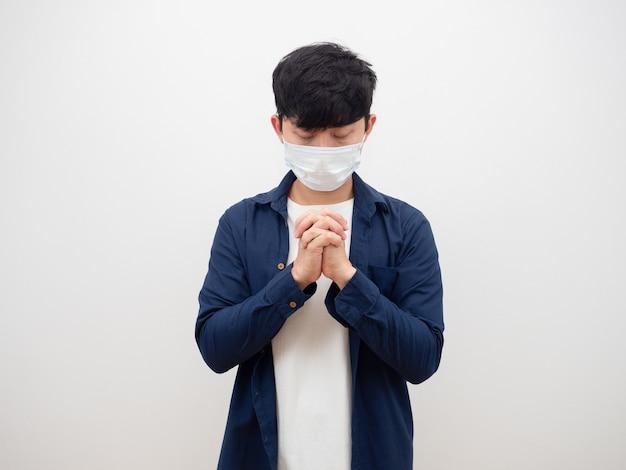 Homme asiatique avec masque gros oeil et priant sur fond blanc contre covid19