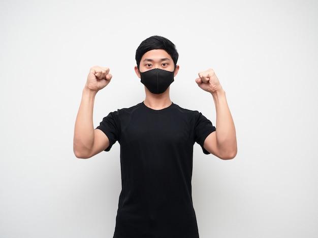 Un homme asiatique avec un masque montre un double poing sur un visage confiant sur fond blanc