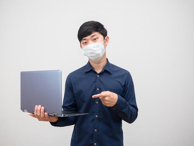 Homme asiatique avec un masque de protection pointant sur un ordinateur portable dans son fond blanc à la main