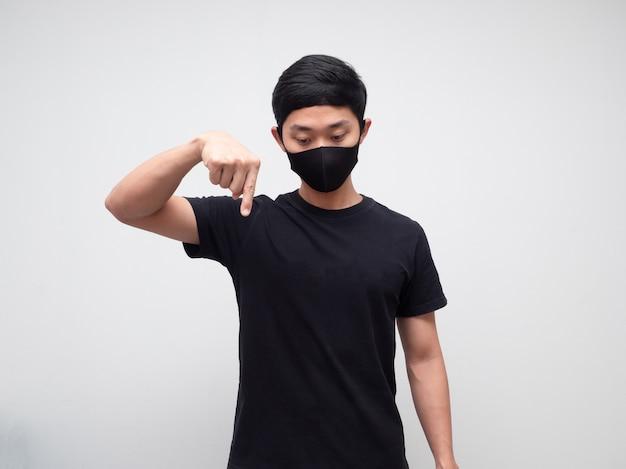 Homme asiatique avec masque de protection pointer le doigt vers le bas